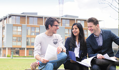 Postgraduate students talking outside the Business School
