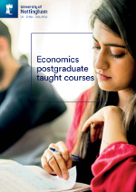 Economics postgraduate taught brochure cover featuring a photography of a student writing