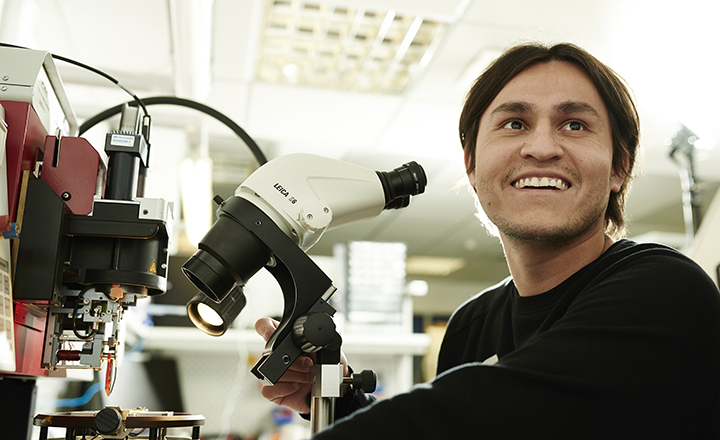 Engineering postgraduate student with microscope