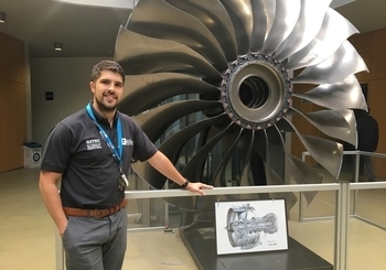 Dr C Hyde standing next to a turbine