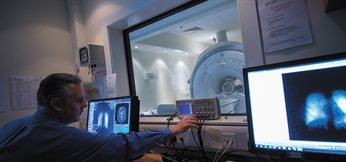 Dr Brett Haywood operating the GE 1.5 Tesla MRI machine from a computer - Medical School, QMC