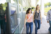 Female students walking past a cash machine