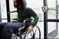 disabled access- male wheelchair user entering a buidling through a disabled access door