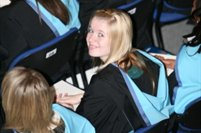 graduation ceremony, female student looking up, smiling.