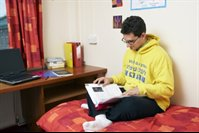 male student studying on a bed in student accommodation