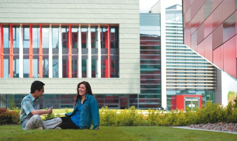 Two postgraduate students sitting on grass in front of Nottingham Geospatial Building, Jubilee Campus