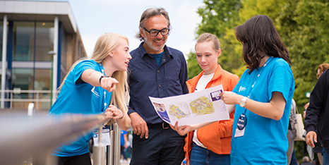 Two student helpers giving a family directions on an Open Day