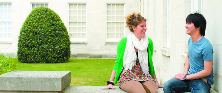 Two students sat outside the Trent Building