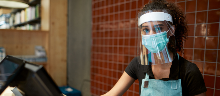 Woman working on a till wearing PPE