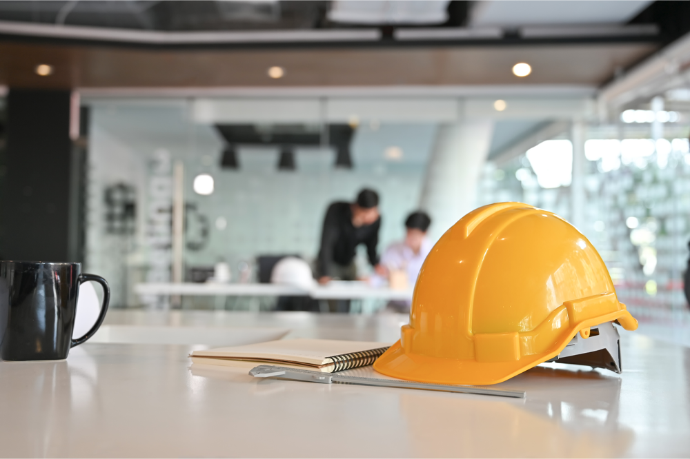 Image of a hard hat resting on a notepad with workers in the distance