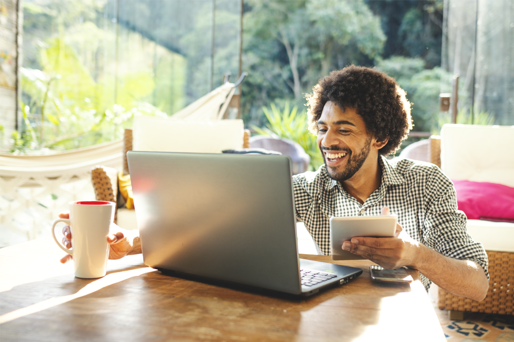 A man working from home with a cup and smiling