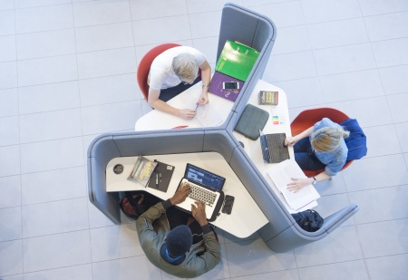 Ariel view of three students working in study booth table