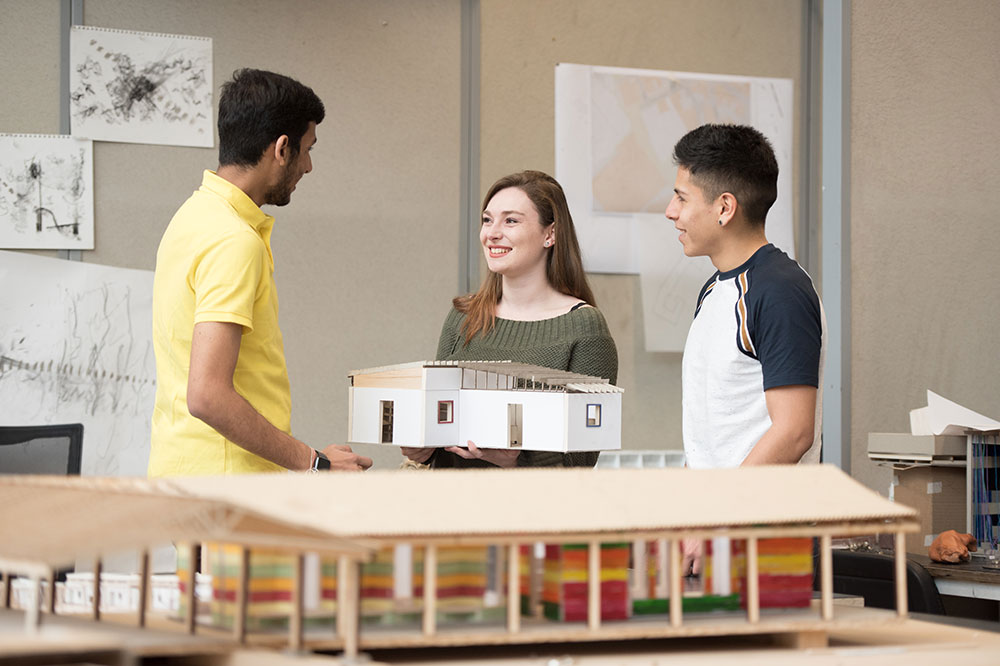 Three students working in a design studio with a house model.