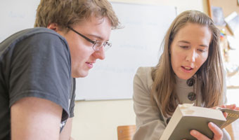 A male student discussing a text with their Personal Tutor