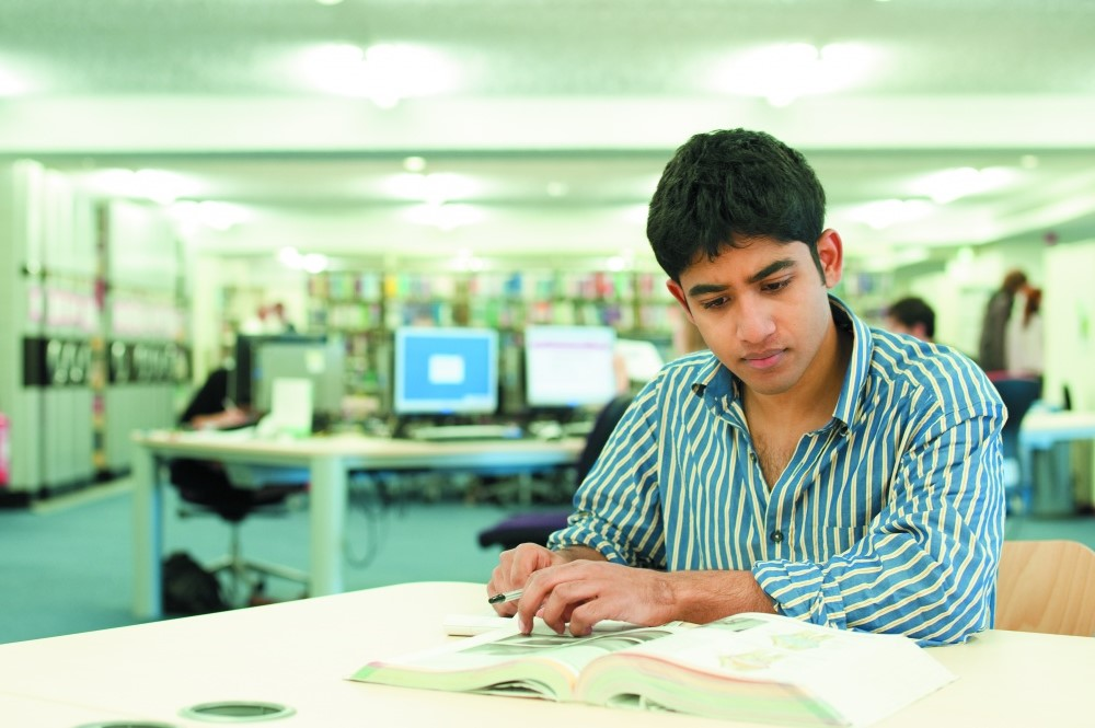 Male student studying in a library