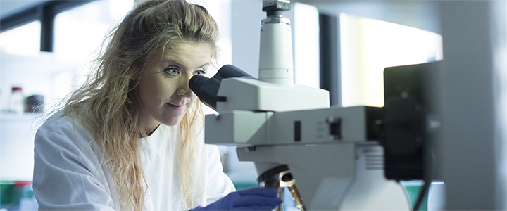 Researcher using a microscope to study cancer cells