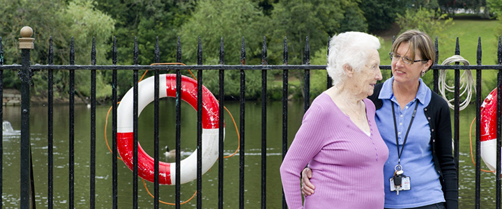 Older person being helped round a boating lake as part of a stroke rehabilitation programme