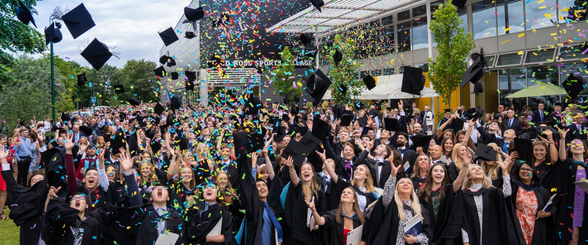 Graduates throwing their mortarboards into the air as confetti rains down