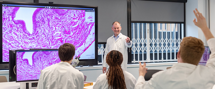 Students in lab coats being taught about cells by a university professor in a specialised lab