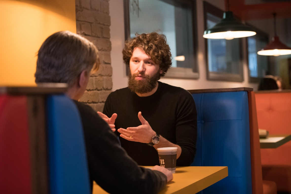 Male student with curly hair and a beard, talking to another person in a cafe