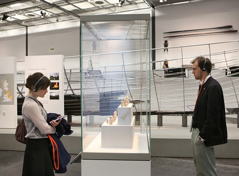 A woman and a man stand either side of a glass case looking at the contents within. Behind them are other museum displays against white walls.