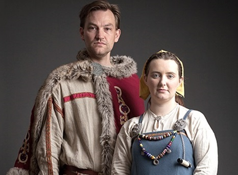 A man and a woman in recreations of traditional Viking garb stand beside each other facing the camera (photo)