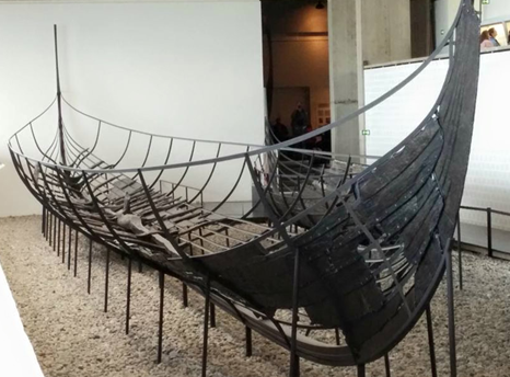 Photograph of a partially reconstructed ancient ship in a museum display
