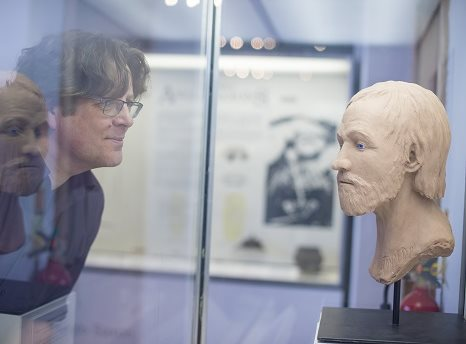 Side shot of a man's face and a sculpted bust inside a glass case facing each other