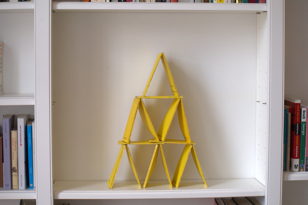 Pyramid of yellow pamphlets in bookshelf