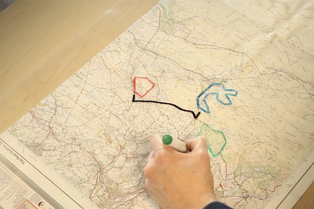 A person drawing on a map, which is part of the Augmented Bird Table