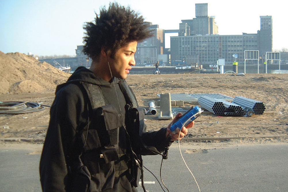 A player holding their handheld device in Can You See Me Now?