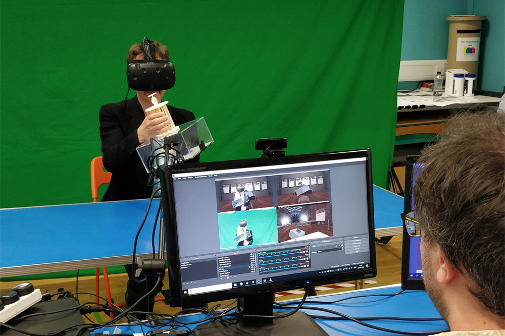 A participant uses the VRtefact system—wearing a VR headset—in front of a green screen, while a researcher watches them