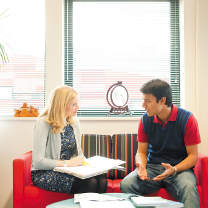 International office staff member chatting with a postgraduate student