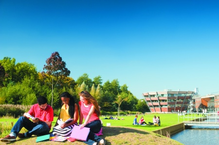 Three students sitting next to the lake on Jubilee campus